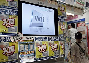 "Men walk near a display showing Nintendo's ""Wii"" game console at a game shop in Tokyo's Akihabara electronic district"